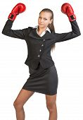 Businesswoman wearing boxing gloves standing in victory pose