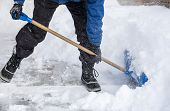 image of snow shovel  - Man bending down and removing snow with a shovel - JPG