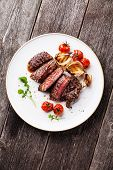 Sliced Medium Rare Grilled Beef Steak Ribeye With Grilled Onions And Cherry Tomatoes On Plate On Woo