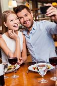 picture of love making  - Beautiful young loving couple making selfie and smiling while sitting at the restaurant together - JPG