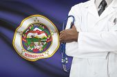 Concept Of National Healthcare System - Minnesota flag on background