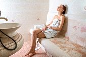 picture of sauna woman  - Young woman in white towel sitting and enjoying in Roman sauna - JPG