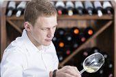 Man Analyzing A White Wine Glass.