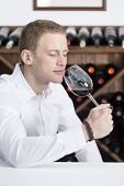 Man Smelling A Red Wineglass.