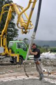 pic of concrete pouring  - Builder uses a concrete pump to direct wet concrete into the foundations of a large building - JPG
