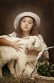 stock photo of baby goat  - Retro styled portrait of a little girl with a baby goat - JPG