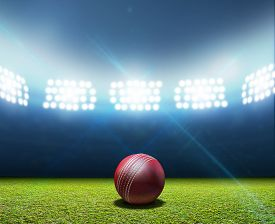 picture of illuminated  - A cricket stadium with a red leather cricket ball on an unmarked green grass pitch at night under illuminated floodlights - JPG