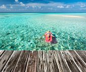 pic of mattress  - Woman relaxing on inflatable mattress at the beach - JPG