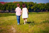 stock photo of girl walking away  - two cute kids walking away on summer field  - JPG