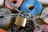 pic of food chain  - box full of tempting delicious donuts wrapped in metal chain and lock in sugar and sweet addiction and diet body and dental care concept - JPG