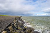 picture of dike  - Deteriorating weather over a dike along a sea in spring - JPG