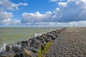 pic of dike  - Deteriorating weather over a dike along a sea in spring - JPG