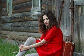 pic of old suitcase  - Portrait of young woman is sitting in front of old log house with vintage suitcase - JPG