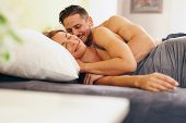 image of enamored  - Enamored young couple lying on bed together in the bedroom - JPG