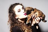 stock photo of little girls photo-models  - Portrait of fashionable young beautiful girl with curly hair and bright make up holding and kissing cute little brown puppy looking forward on light grey background horizontal picture - JPG