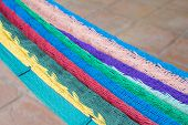 image of mexican  - Shallow depth of focus on hanging multi-colored Mexican hammock with blurred Mexican tile floor as background with copy space ** Note: Shallow depth of field - JPG