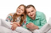 stock photo of laying-in-bed  - Happy smiling couple laying laughing in bed on white background - JPG