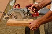 image of worm  - Building contractor worker using hand held worm drive circular saw to cut boards on a new home construciton project - JPG