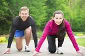 stock photo of competing  - Young sport couple in starting position prepared to compete and run - JPG
