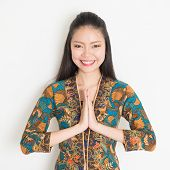 picture of southeast asian  - Portrait of happy Southeast Asian woman with batik dress in greeting gesture on plain background - JPG