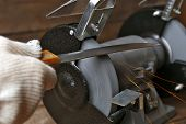 stock photo of friction  - Knife sharpener and hand with blade on wooden table - JPG