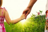 picture of helping others  - Hands of mother and daughter holding each other on field - JPG