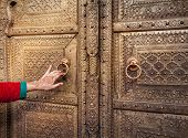 picture of rajasthani  - Woman hand with henna painting opening golden door in City Palace of Jaipur Rajasthan India - JPG