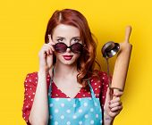 stock photo of plunger  - Surprised redhead girl in red polka dot dress with plunger on yellow background - JPG
