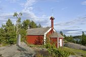 picture of chapels  - Red wooden chapel in sunny evening lit by the sea - JPG
