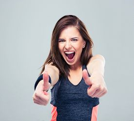 picture of screaming  - Sports woman showing thumbs up and screaming over gray background - JPG