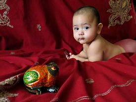 image of baby frog  - Baby boy lies on the Indian silver embroidered dark - JPG
