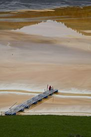stock photo of polution  - poluted lake with a bridge and a lone man standing on it - JPG