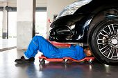 Mechanic In Blue Uniform Lying Down And Working Under Car At Auto Service Garage poster
