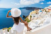 Tourist woman enjoying view of beautiful white village of Oia with Caldera and mediterranean sea. Yo poster