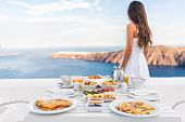 Breakfast table and luxury travel woman on santorini. Well balanced perfect breakfast table served a poster