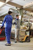 Carpenter and apprentice in workshop