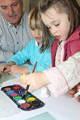 Senior man making watercolors with children
