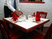 Waiter Setting Table In Restaurant