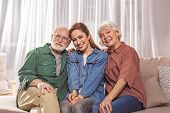 Portrait Of Cheerful Bearded Grandfather Sitting Near Glad Daughter And Outgoing Wife On Sofa. They  poster