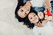 Top View Portrait Of Content Mother And Child Resting On Rug With Teddy Bear. Copy Space In Left Sid poster