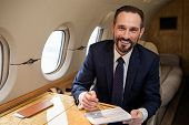 Portrait Of Glad Handsome Businessman In Airplane Cabin Sitting At Table With Some Documentation. He poster