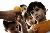 Refugee camp, poverty, hungry children receiving humanitarian food