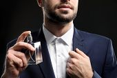 Handsome man in formal suit and with bottle of perfume on dark background, closeup poster