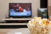 Popcorn And Remote Control On Sofa With A Tv Broadcasting Wrestling On Background poster