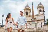 Happy romantic couple holding hands on Spanish Steps in Rome, Italy. Joyful young interracial couple poster