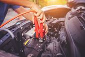 Close Up Of Auto Mechanic Jumping Battery Car,check Voltage Level Car Battery,helping Concept. poster