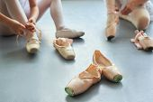 Ballet Pointe Shoes, Blurred Background. Ballerina Putting On Ballet Slippers Sitting On The Floor.  poster