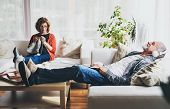Happy Senior Couple Relaxing At Home. A Woman Knitting And A Man With Tablet Listening To Music. poster