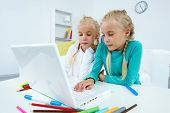 image of cute little girl  - Portrait of twin girls studying in front of laptop - JPG