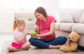 Little Girl And Her Pregnant Mom Eating Salad Sitting On Floor At Home. Motherhood, Healthy Eating A poster